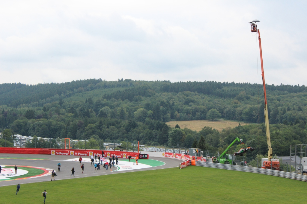 Paul Di Resta's car being hauled away over the pit entrance at the Bus Stop Chicane